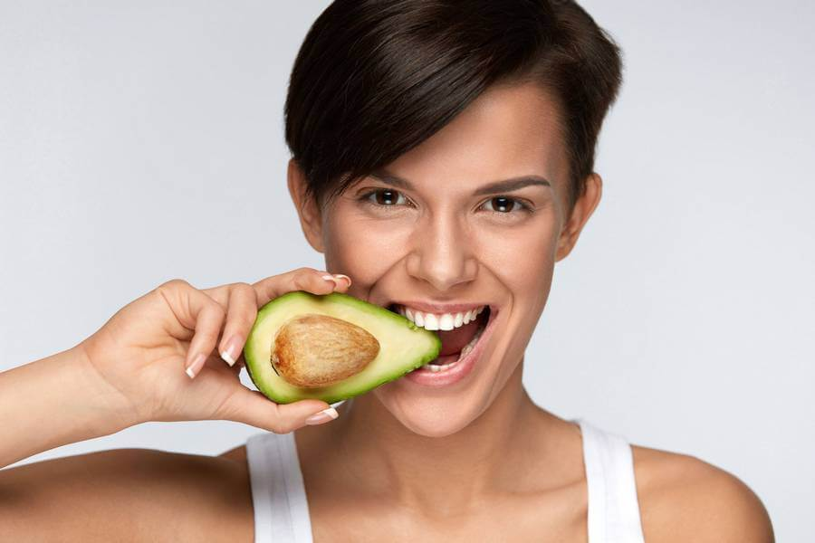 mujer comiendo aguacate